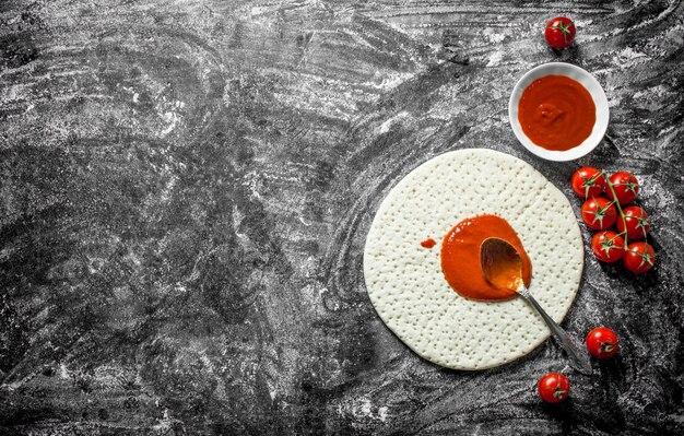 Preparación de pizza. masa enrollada con pasta de tomate y tomates frescos. sobre fondo rústico