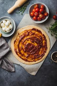 Preparación de pizza pizza cruda estire la masa integral en bandejas para hornear con varios ingredientes para cocinar pimienta, mozzarella, tomate, salsa de tomate, tomillo y rodillo.