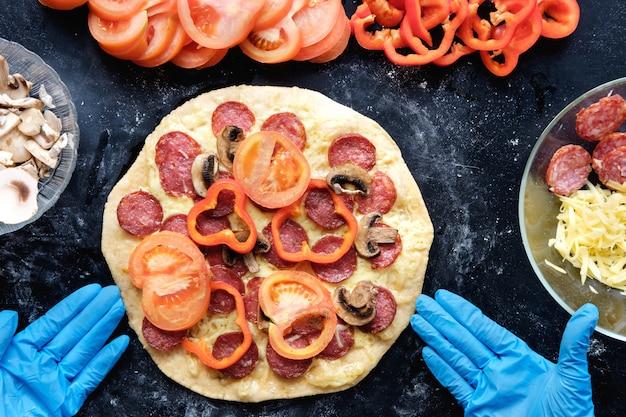 Preparación de pizza en restaurante en guantes de silicona, vista superior