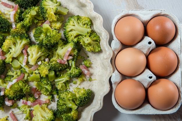 Preparación de quiche con brócoli, huevos y tocino