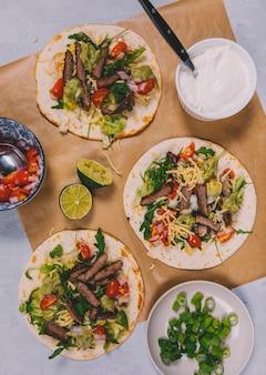 Preparación de tacos mexicanos con carne y verduras.