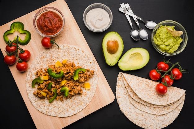 Preparación de tacos en tabla de cortar junto a verduras y salsas.