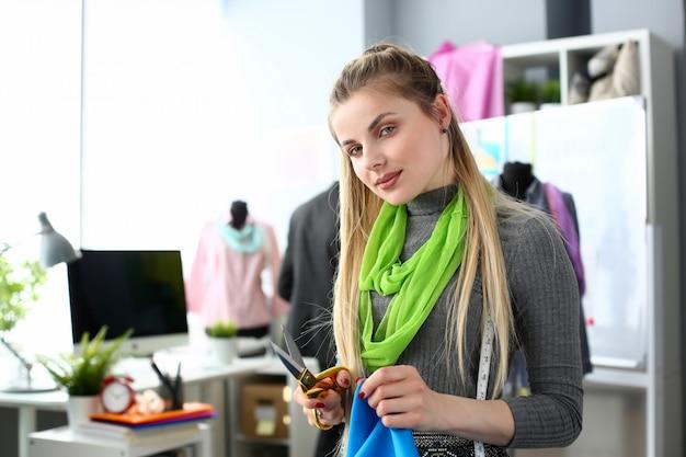 Preparación de textiles para la confección de prendas de vestir de moda. needlewoman atractivo con tijeras y muestra de tela.