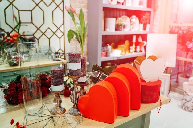 Preparación para unas vacaciones con cajas rojas en forma de corazón, velas, regalos, flores en la habitación.