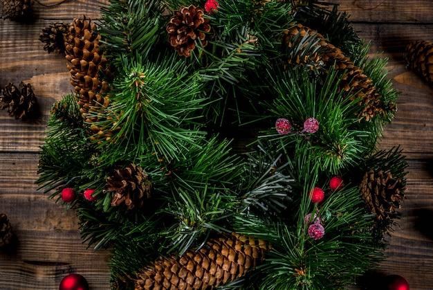 Preparación para vacaciones de navidad. guirnalda verde decorativa de navidad con piñas y bayas rojas de invierno y bolas de árboles de navidad