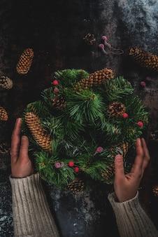 Preparación para vacaciones de navidad. mujer que adorna la guirnalda verde de navidad con piñas y bayas rojas de invierno, en copyspace oxidado oscuro, vista superior, manos femeninas