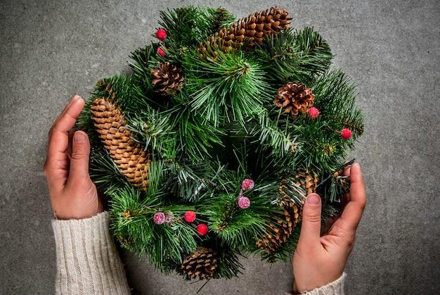 Preparación para vacaciones de navidad. mujer que adorna la guirnalda verde de navidad con piñas y bayas rojas de invierno