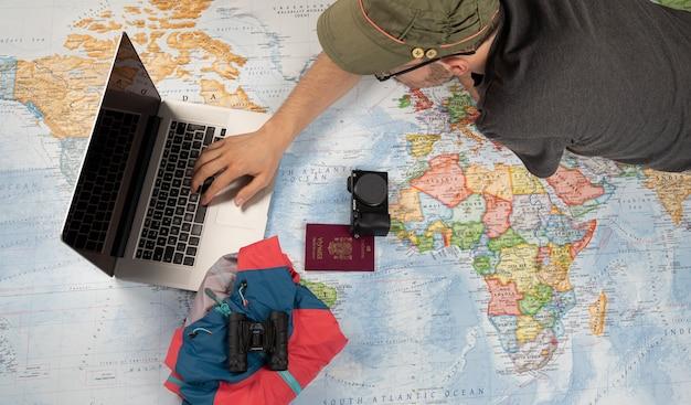 Preparación del viaje con computadora portátil, binoculares y chaqueta en un mapa mundial.
