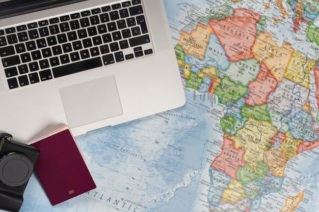 Preparación del viaje con computadora portátil y pasaporte en un mapa mundial.