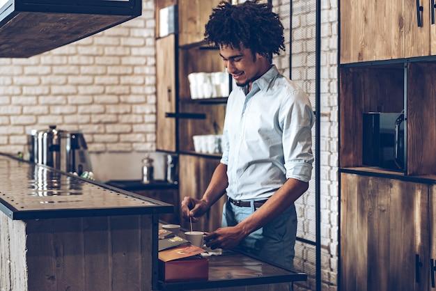 Preparando café. joven africano revolviendo el café con una sonrisa mientras está de pie en la barra de bar