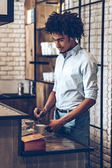 Preparando café para su cliente. vista lateral del joven africano revolviendo el café