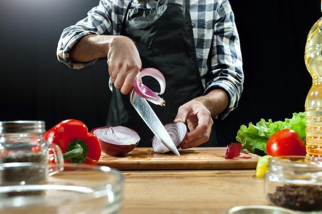Preparando ensalada. chef mujer cortando verduras frescas.