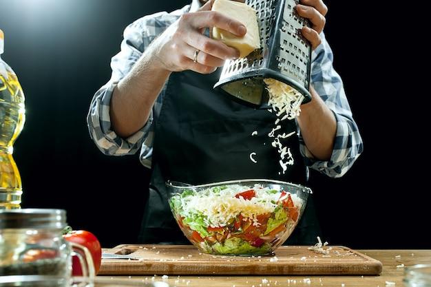 Preparando ensalada. chef mujer cortar verduras frescas. proceso de cocción. enfoque selectivo