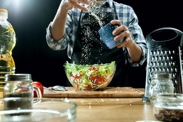 Preparando ensalada. chef mujer cortar verduras frescas.