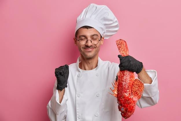 Preparando mariscos. feliz chef europeo en uniforme de cocinero, guantes de goma sostiene lubina roja, aprieta el puño con alegría