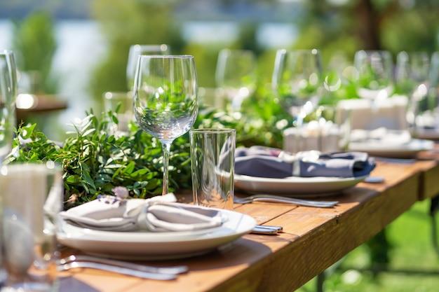Preparándose para una fiesta al aire libre. decorado con flores frescas servidas mesas. número de mesa detalles de decoración.