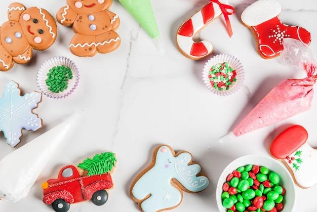 Preparándose para navidad, decorando pan de jengibre tradicional con glaseado de azúcar multicolor, galletas, glaseado en paquetes sobre una mesa de mármol blanco. marco de vista superior