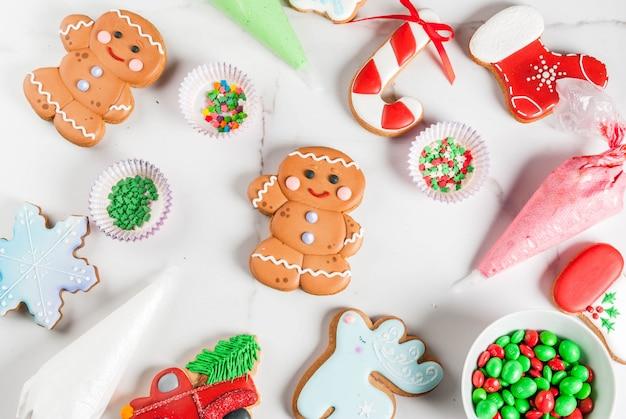 Preparándose para navidad, decorando pan de jengibre tradicional con glaseado de azúcar multicolor, galletas, glaseado en paquetes sobre una mesa de mármol blanco. vista superior