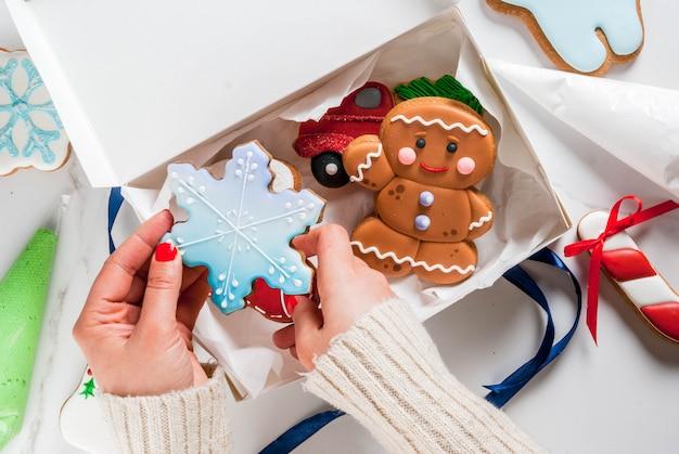 Preparándose para navidad, decorando pan de jengibre tradicional con glaseado de azúcar multicolor, la niña sostiene las galletas
