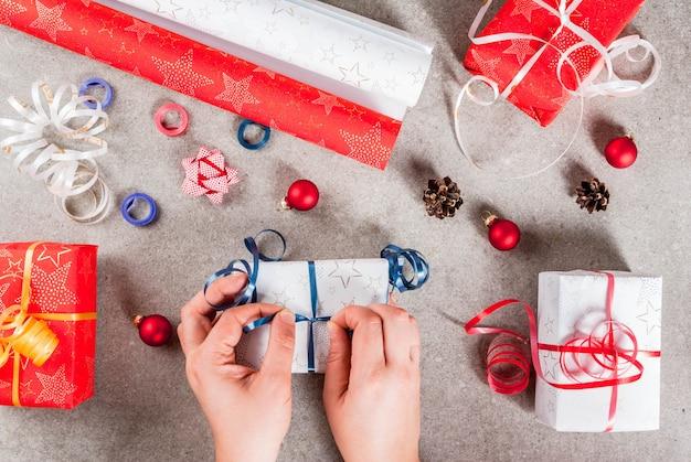 Preparándose para las vacaciones de navidad. regalos y decoraciones en la mesa, las manos de la niña en la imagen ata la cinta del regalo. vista superior
