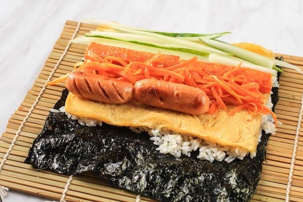 Preparar hacer un rollo coreano de gimbap kimbob o kimbap hecho con bap de arroz blanco al vapor