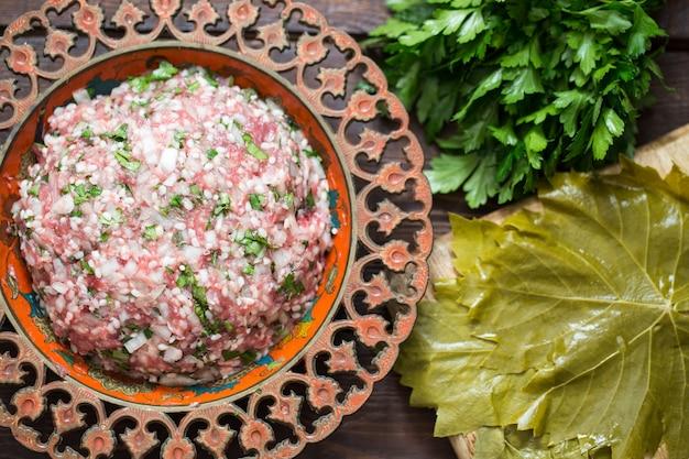 Preparar hojas de parra rellenas con arroz y carne, o dolma tradicional. vista superior