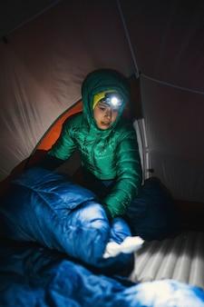Preparar un saco de dormir en una tienda de campaña para la noche fría.