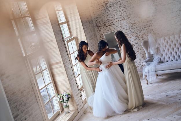 Preparativos importantes. vista superior de longitud completa de dos atractivas mujeres jóvenes que se ponen un vestido de novia en una novia mientras están de pie juntos junto a la ventana