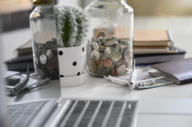Preparativos de viaje con ahorro de dinero en el escritorio de oficina.