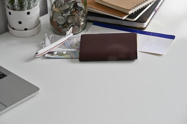 Preparativos de viaje, pasaporte, boleto de avión y mapa en la mesa de la oficina.