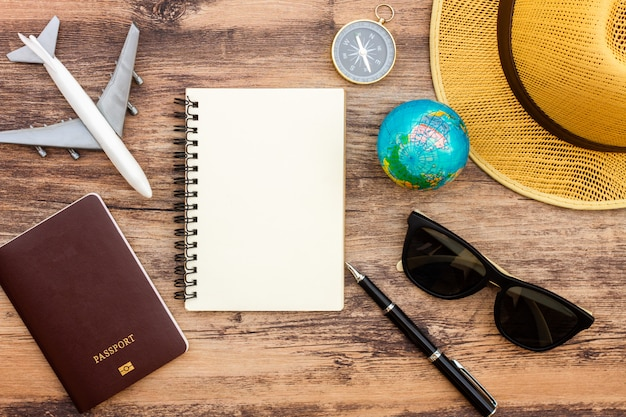 Prepare accesorios y artículos de viaje sobre tabla de madera, fondo plano, vista superior