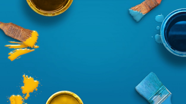 Prepare el concepto de pintura con pinceles de color y cajas de color en la superficie azul. vista superior, plano, primer plano.