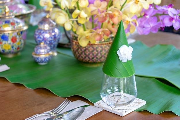 Prepare el juego en la mesa para la vajilla de plata de la comida tailandesa y el vidrio con hoja de plátano