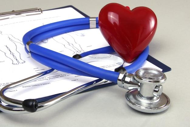 Prescripción rx, corazón rojo y un estetoscopio sobre blanco.