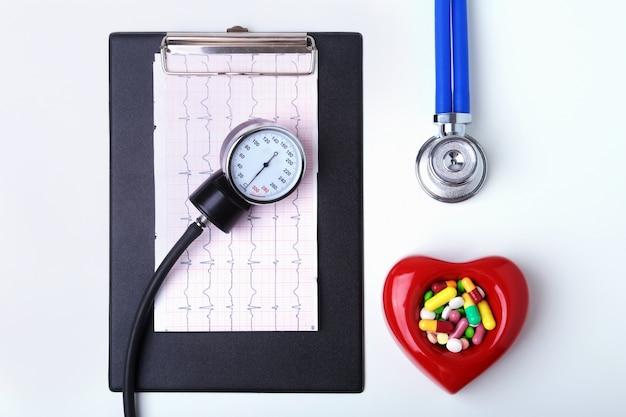 Prescripción de rx, corazón rojo, pils surtidos y un estetoscopio sobre fondo blanco