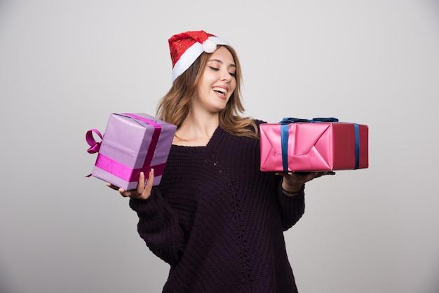 Presenta mujer joven con sombrero de santa con cajas de regalo.