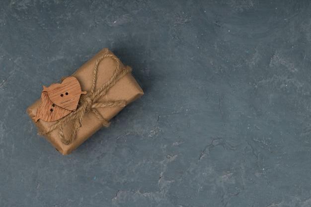 Presenta en papel artesanal decorado con corazones de madera sobre fondo de hormigón, copia espacio. embalaje ecológico de san valentín o cumpleaños.