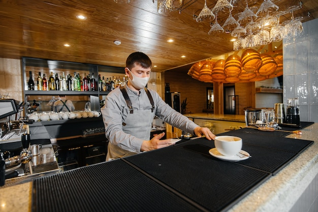 Presentación de un barista con una máscara de delicioso café orgánico en un café moderno durante la pandemia.