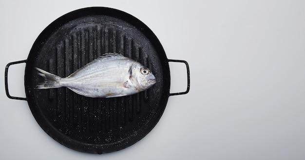 Presentación de besugo silvestre fresco en sartén grill listo para cocinar