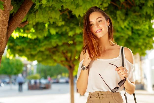 Presentación caucásica hermosa joven de la mujer al aire libre en la ciudad