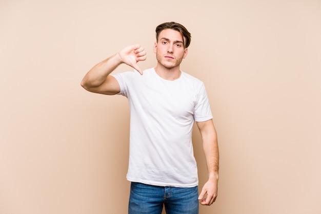 Presentación caucásica joven del hombre aislada mostrando un gesto de la aversión, pulgares abajo. concepto de desacuerdo
