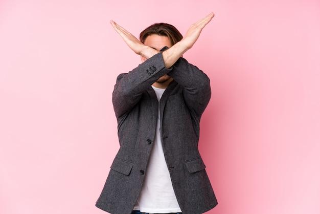 Presentación caucásica joven del hombre de negocios aislada manteniendo dos brazos cruzados, concepto de la negación.