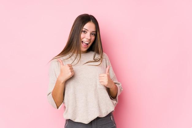Presentación caucásica joven de la mujer aislada levantando ambos pulgares para arriba, sonriendo y confiados.