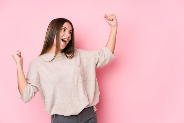 Presentación caucásica joven de la mujer aislada levantando el puño después de una victoria, concepto del ganador.