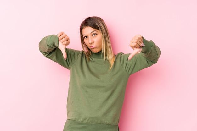 Presentación caucásica joven de la mujer aislada mostrando el pulgar hacia abajo y expresando aversión.