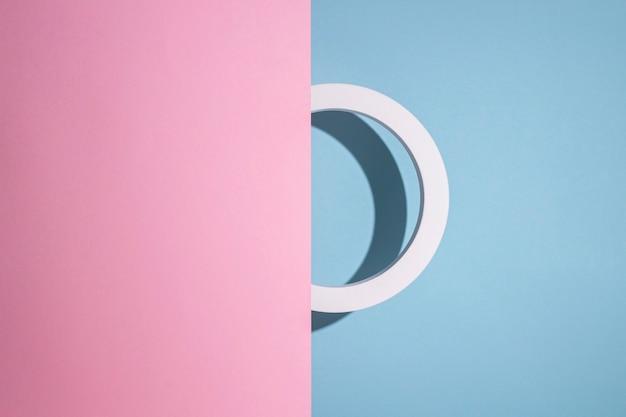 La presentación del círculo del podio se asoma desde un fondo de cartón rosa se asoma sobre un fondo azul