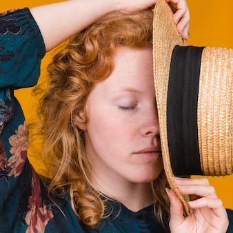 Presentación femenina bonita joven con la cara de la cubierta del sombrero