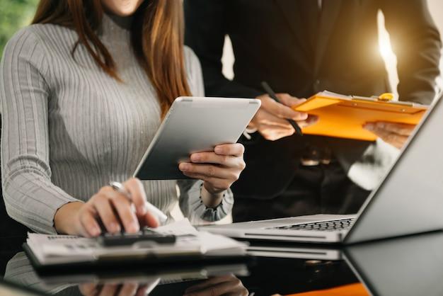 Presentación de la reunión de negocios del equipo. proyecto de trabajo de empresario de mano en la oficina moderna. computadora portátil y tableta y teléfono inteligente en el escritorio blanco en la luz de la mañana