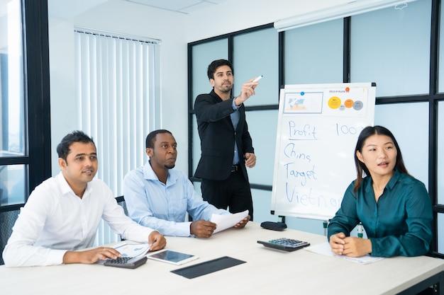 Presentador guapo serio que muestra a un lado mientras explica los datos en la reunión.