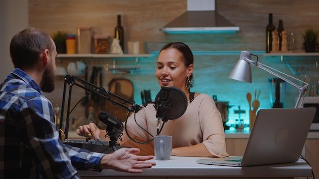 Presentador de programas de internet entrevistando a un invitado en un estudio en casa para un podcast utilizando un micrófono profesional. programa en línea creativo onair presentador de transmisión de producción que transmite contenido en vivo grabando medios digitales